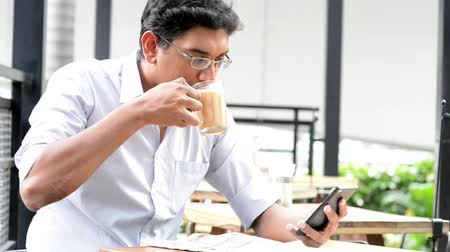 holding newspaper : Asian Indian businessman using smartphone at cafeteria
