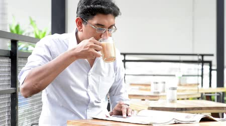 indian tea : Asian Indian business man reading newspaper while drinking a cup hot milk tea during lunch hour at cafeteria.