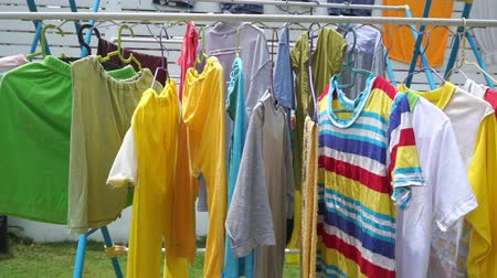 vállfa : Clothes drying on the clothesline outside on a sunny day, footage video. Stock mozgókép