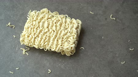 sponka : A block of Asian ramen instant noodles dropping and cracks on table background, footage video. Dostupné videozáznamy