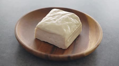 soya peyniri : Uncooked tofu block on plate rotating, footage video.