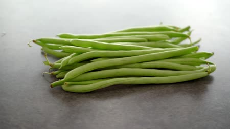 turn table : Raw green French beans on grey table rotating footage video. Stock Footage