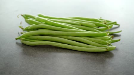 stacks : Raw green French beans on grey table rotating footage video. Stock Footage