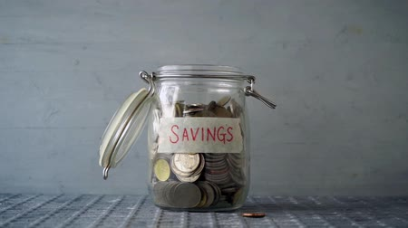 piggy bank : Slow motion coin money dropped into glass jar with savings label, financial concept. Stock Footage
