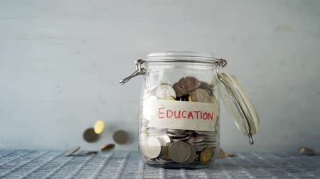 ipuçları : Slow motion coin money dropped into glass jar with education label, financial concept.