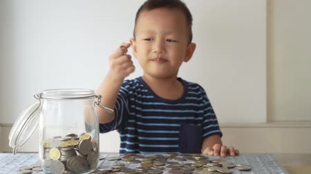 malajské : Slow motion child drops coin money into glass jar, financial concept.