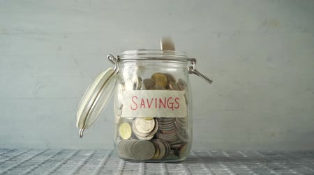salva vidas : Slow motion coin money dropped into glass jar with savings label, financial concept. Vídeos