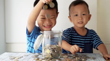 malajské : Slow motion children drops coin money into glass jar, financial concept.