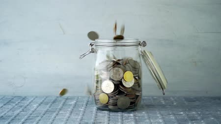 pensão : Slow motion coin money dropped into glass jar, financial concept.