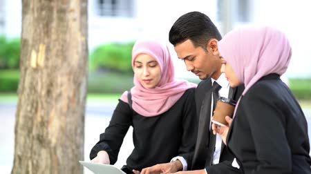 Muslim business people discussion with laptop, outdoor.
