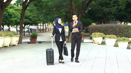 Business people walking and discussing, using tablet pc outdoor. Stockvideo