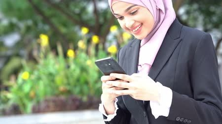 Muslim business woman using smartphone and smiling.
