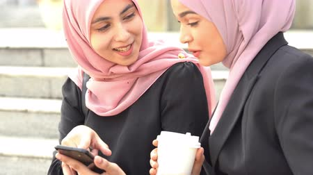 Muslim women using smart phone, sharing and laughing.