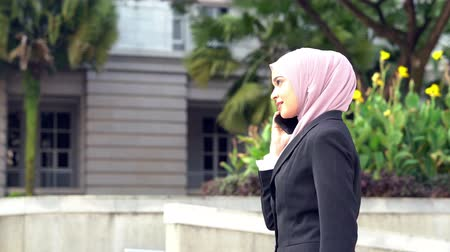 マレー語 : Muslim business woman talking on the phone while walking.