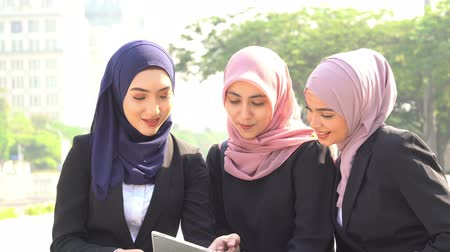 Muslim business women using tablet pc and laughing together.