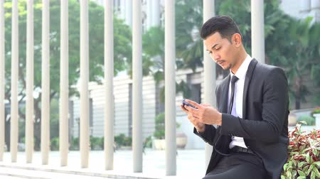 Businessman using mobile phone outdoor during office hour.