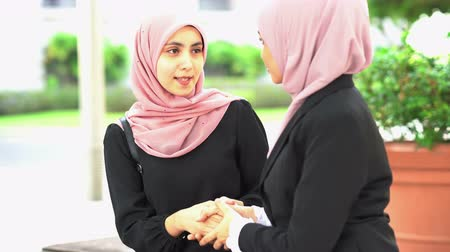 Muslim business women greeting, handshake and smiling.