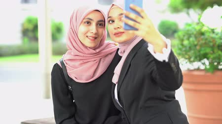 Muslim woman taking self photo, using smartphone camera.