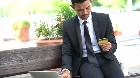 Outdoor business man using laptop and credit card.
