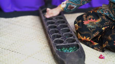 Woman hand playing congkak, traditional Malay two player game in which seeds or marbles are dropped into depressions carved into a boat-shaped wooden board. Stockvideo