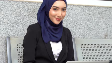 Muslim business woman smiling, using laptop computer.