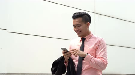 Businessman reading on mobile phone and smile while walking outdoor.