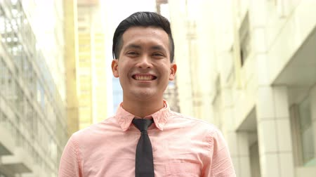 malaya : Young entrepreneur smile cheerfully outdoor, urban background. Stok Video