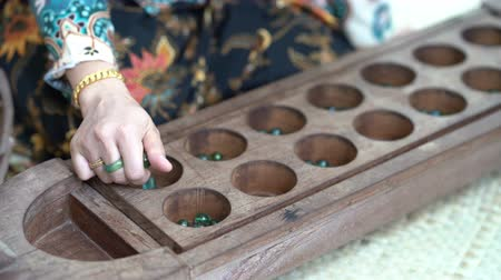 Woman hand playing congkak, traditional Malay two player game in which seeds or marbles are dropped into depressions carved into a boat-shaped wooden board. Стоковые видеозаписи