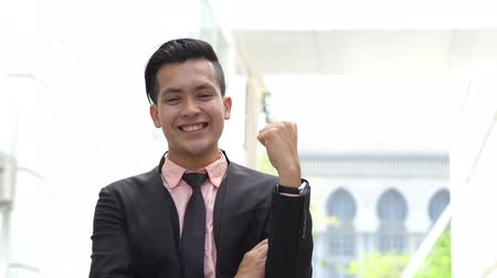 malaya : Young business man smile cheerfully outdoor, celebrating success, urban background. Stok Video