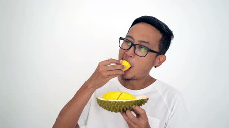с шипами : Man eating durian, on white background. Стоковые видеозаписи