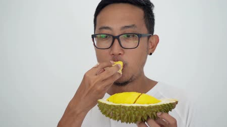 mal cheiroso : Man eating durian, on white background. Stock Footage