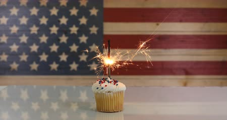 queque : Vanilla cupcake and burning sparkler with rustic wooden United States Flag in background. July 4th holiday concept in 4k footage format.