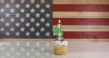 veterano : Vanilla cupcake and number four candle with rustic wooden United States Flag in background. July 4th holiday concept in 4K footage format.