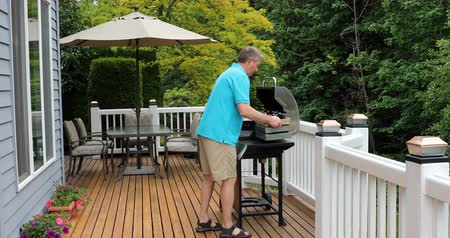 кедр : Mature man taking wooden box filled with bottled beer to BBQ cooker on outdoor cedar deck.