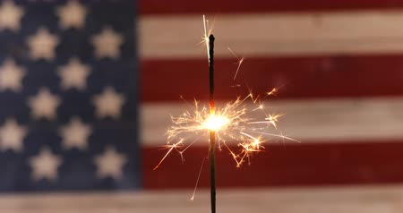 июль : Burning sparkler with rustic wooden United States Flag in background for Independence Day celebration. Стоковые видеозаписи