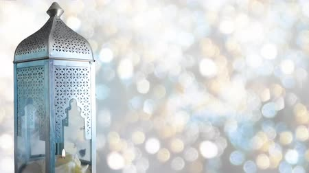 srebro : Arabic ornamental lantern with burning candle and glittering bokeh lights background, loopable Ramadan HD footage Wideo