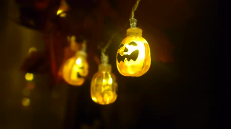 Halloween or Dia de los Muertos party decoration, lighting. Swinging string of  pumpkin lights and leaves. Closeup HD footage.