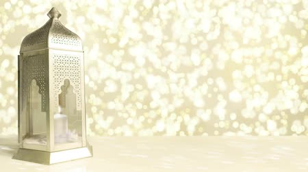 Arabic ornamental lantern with burning candle and glittering golden background with falling bokeh lights. Ramadan HD footage. Stock mozgókép