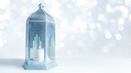 Arabic ornamental lantern with burning candle and glittering silver and blue background with bokeh lights. Loopable Ramadan HD footage. Stock mozgókép