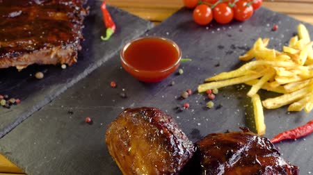 barbecue set : grilled bbq pork meat and potatoes on stone plate Stock Footage
