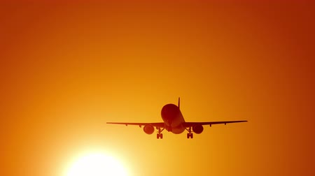 A large passenger plane takes off against the background of a sunset. Orange backgrand..Super slow motion. Filmati Stock