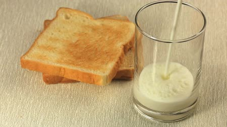 Simple breakfast with toasts and a glass of fresh milk. Stok Video