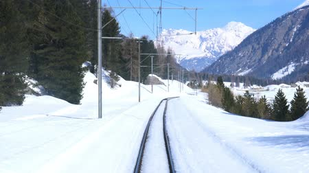 View of snowy Alpine Mountain Railway from St. Moritz Switzerland to Tirano Italy Stok Video