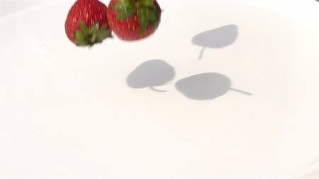 Strawberries falling on the water in white plate in Slow Motion Stok Video