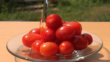 Pouring fresh water to a pile of Grape Tomatoes in a glass plate in Slow Motion
