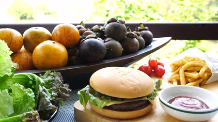 Fresh vegetables, natural fruit, french fries and tasty beef hamburger on wooden cutting board
