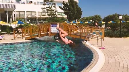 yerleşim : Young man does front flip dive into pool. Stok Video