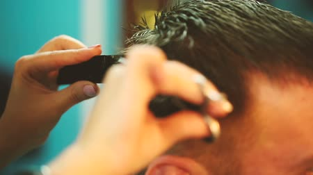 kuaför : Hairdresser working with scissors and cuts a young man with a beard. Stok Video