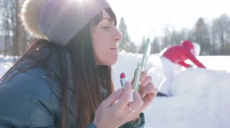 ruj : Girl applies lipstick winter outdoors