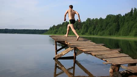 наслаждаться : Jump in a lake with wooden walkways